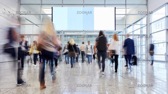 Messe Besucher gehen unter großer Werbefläche