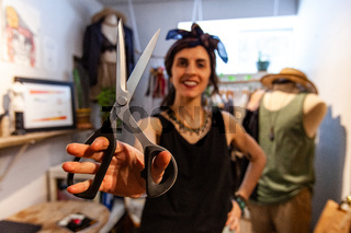 Fashion designer showing sewing scissors