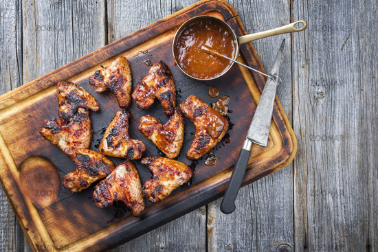 Traditional barbecue chicken wings with hot chili sauce as top view on a burnt cutting board