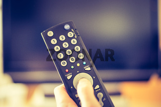 Male hand is holding TV remote control, smart TV.