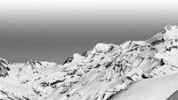 Snowy mountain and off-piste slope with trace from skis and snowboards
