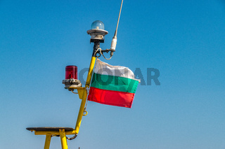 Bulgaria Flag on a Fishing Boat at a harbor port in Nessebar ancient city on the Bulgarian Black Sea Coast. Bulgarian Flag against a blue sky
