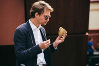 Successful And Handsome Young Man In Office Clothes Eating A Sandwich On The Street At Lunchtime