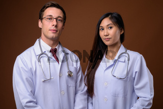 Studio shot of two young doctors together against brown backgrou