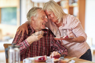 Senioren Paar umarmt sich beim Kuchen essen