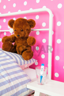 Pink bedroom with toy bear and thermometer