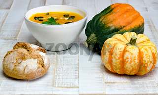 organic pumpkin soup in a white bowl framed by pumpkins and whole flour bread