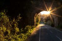 Sunlit arch over a bicycle path in Italy