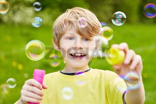 Kind macht viele Seifenblasen im Sommer