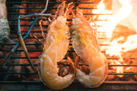 Fresh grilled Lobster grilling on outside open flame Barbeque at a street food market restaurant in Asia