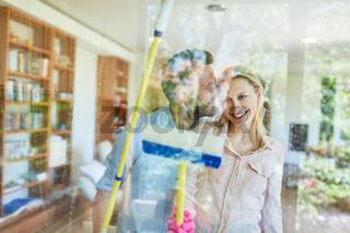 Glückliches junges Paar beim Fenster Glas putzen