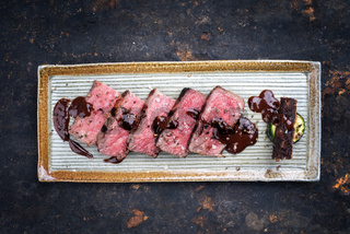 Barbecue wagyu aged fillet steak slices with brownie and chili chocolate sauce as top view on a plate