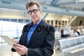 Selbstbewusster Manager auf Dienstreise mit Tablet PC