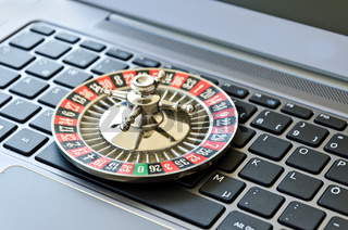 Roulette wheel lying on computer keyboard symbolizing online gambling