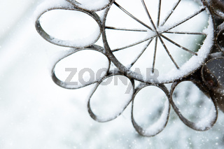 Snow-covered gray stainless steel Flower. Winter background with snow.