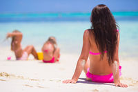 Little girls and happy mother during beach vacation