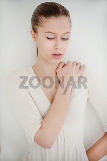 a young thoughtful Woman in white dress about walls