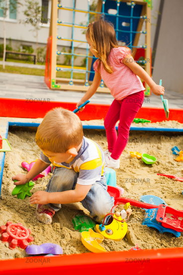 Happy children sitting in sandbox playing with plastic colorful toys.