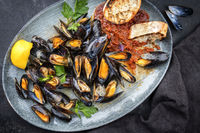 Traditional barbecue Italian blue mussel in tomato sauce with parsley and garlic in red wine sauce as top view on modern design plate