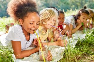 Durstige multikulturelle Kinder trinken Wasser