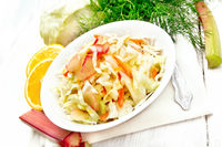 Salad of cabbage and rhubarb in plate on white board