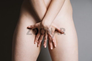 unrecognizable naked woman covering her private parts