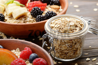 Glass gar with oats with bowl of muesli and berries aside closeup