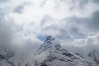 Gray high mountain peaks covered with ice and sky with clouds
