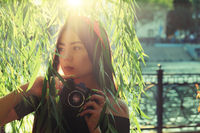 Asian Girl with camera in the park in sunset time. Brunette girl with film camera in the vintage colored image posing against willow branches