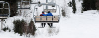 Two skiers on chair-lift in gray day