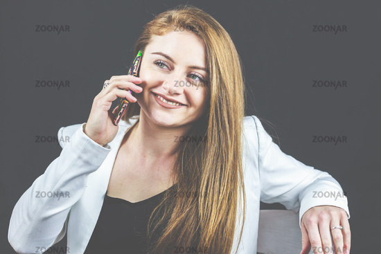 Young woman in jeans and white blazer holding her smartphone, talking on the phone and reading news.