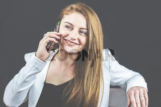 Junge Frau mit Jeans und weißem Blazer hält Ihr Smartphone in der Hand, telefoniert und liest Nachrichten.