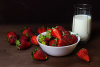Fresh strawberries in ceramic bowl and a glass of milk  on dark wooden background. Selective focus