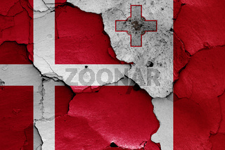 flags of Denmark and Malta painted on cracked wall