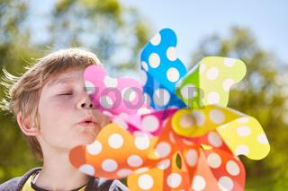 Kleiner Junge pustet gegen ein buntes Windrad