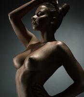 Gold skin woman artistic nude studio portrait
