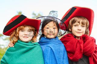 Drei Kinder in bunten Kostümen im Fasching