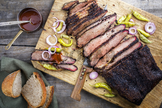 Traditional smoked barbecue wagyu beef brisket offered with farmhouse bread as top view on an old cutting board with Louisiana sauce