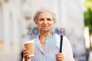 senior woman drinking coffee at summer city