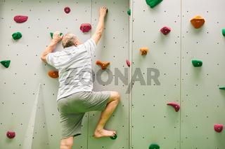 Senior Mann beim Klettern in Kletterhalle