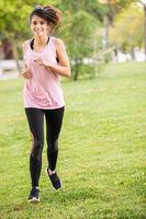 Dark-haired girl in sportswear running in the park.