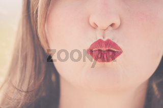 Cherry red lips of young girl are kissing