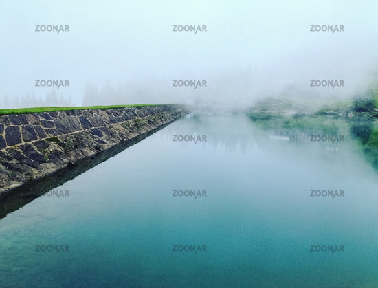 Mist and fog over a lake on a winter day in a humid forest, film grain added.