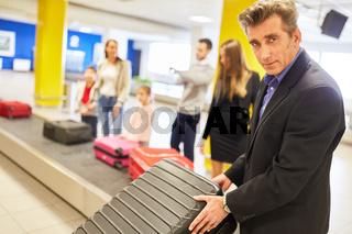 Business Mann auf Dienstreise am Gepäckband