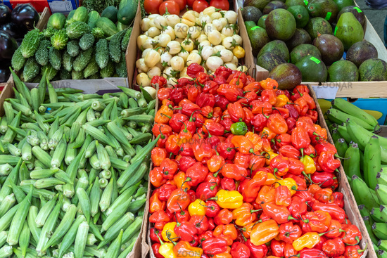 Mini bell peppers, pickles and peas for sale at a market