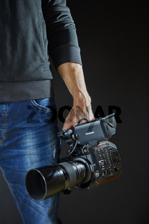 Kiev, Ukraine - April 22, 2018: Photographer and video maker man hold Panasonic AU-EVA1 video camera on his hand to making footage