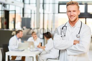 Junger Mann als lächelnder Arzt in der Ausbildung