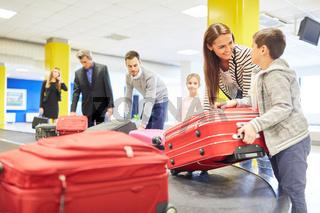 Familie und andere Passagiere holen ihre Koffer