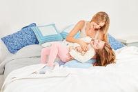 Fröhliche Mutter kitzelt ihre Tochter beim Spielen