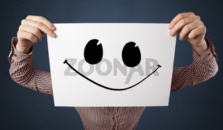 Person holding a paper with funny emoticon in front of her face